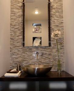 A powder room is a perfect place to add an accent wall. This can be done with paint, wallpaper, or in this case tile.